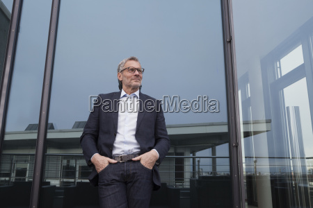 successful businessman standing on office terrace