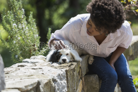 young woman stroking her dog on