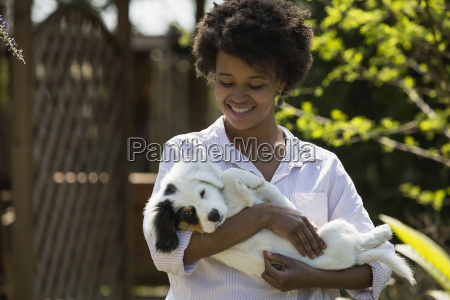 happy young woman holding dog in
