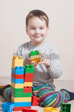spielen des kleinen jungen mit farbigen