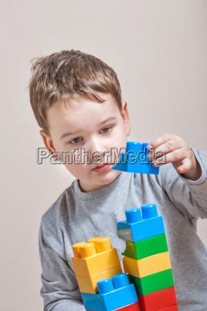 einen kleinen jungen mit farbigen wuerfeln