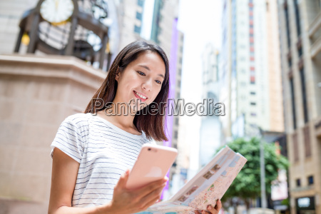 young woman using gps and city