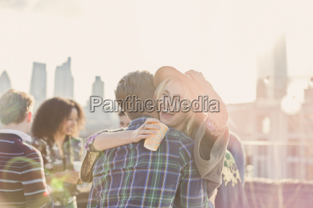 enthusiastic young woman hugging man at