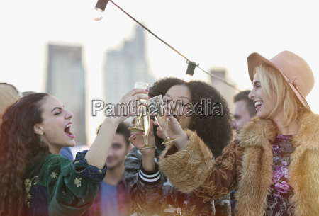 enthusiastic young women toasting champagne glasses