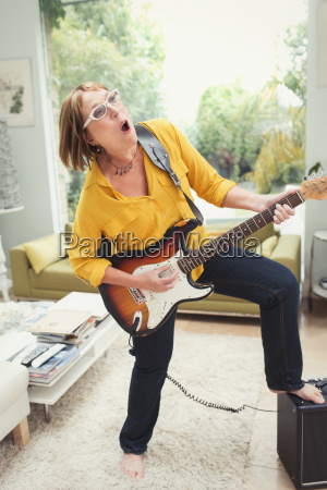 playful mature woman playing electric guitar