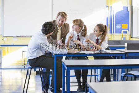 teacher teaching high school students assembling