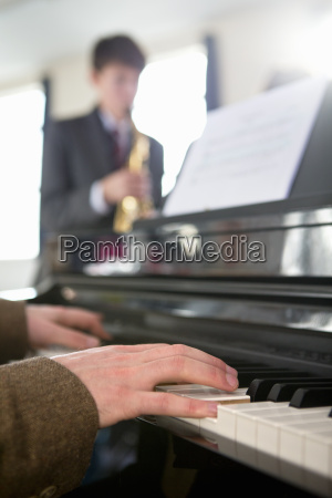 music teacher playing piano with high