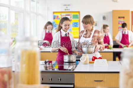 teacher guiding student cooking in home