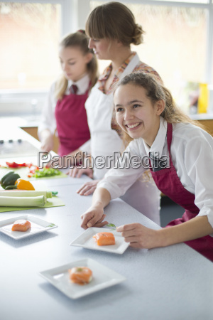 smiling high school student plating food