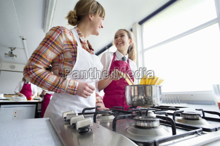 smiling teacher and student cooking pasta