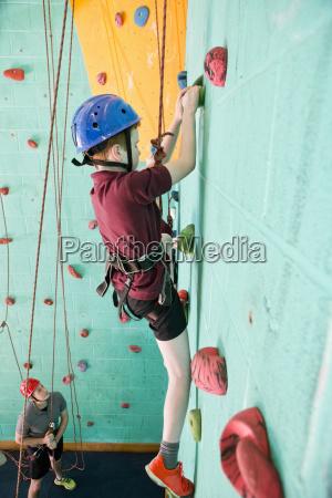 boy climbing rock climbing wall