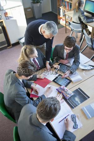math teacher guiding high school students