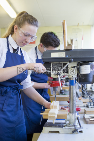 female high school student using drill