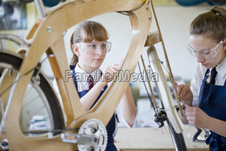 female high school students assembling bicycle
