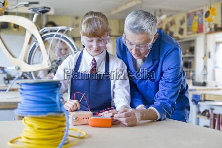 teacher guiding female high school student