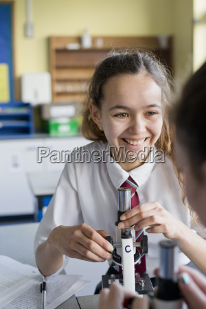 smiling high school student using microscope