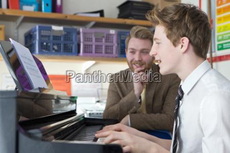 teacher teaching high school student playing