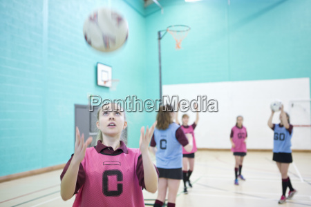high school student catching netball in