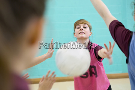 high school student throwing netball in