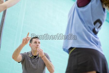 gym teacher with whistle teaching high