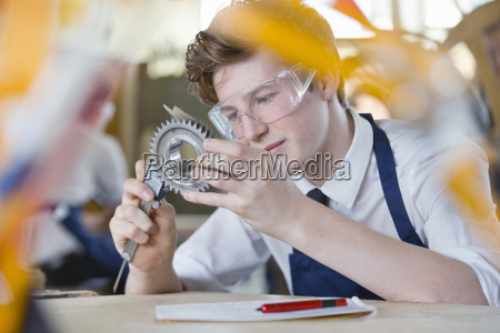 high school student measuring cog with