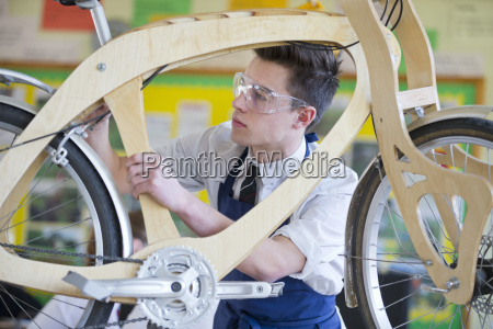 high school student assembling bicycle in