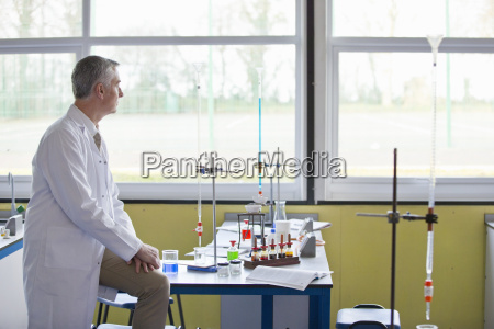 pensive chemistry teacher looking out science