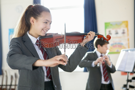 smiling high school student playing violin