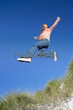 exuberant girl jumping for joy over