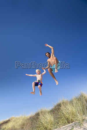 father and son jumping for joy