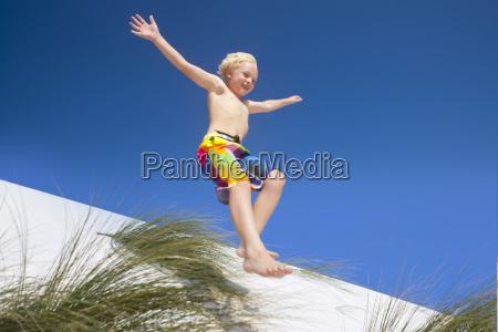 exuberant boy jumping for joy over