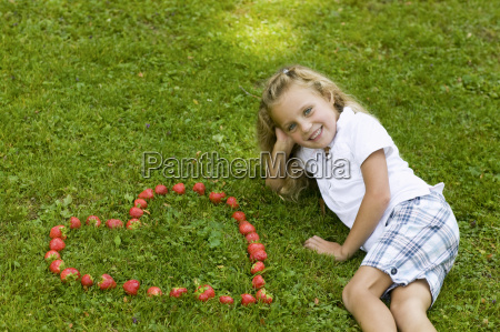 girl posing with heart shaped strawberries