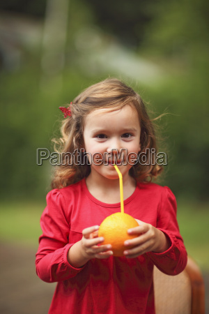 a young girl drinking orange juice