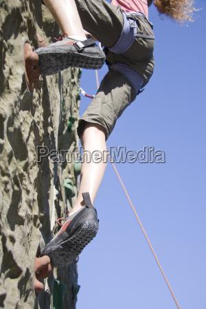 a young girl scaling a climbing