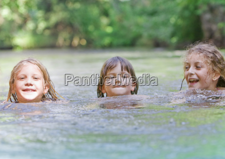 three young girls swimming together in