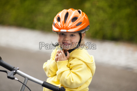 young girl riding bicycle with helmet