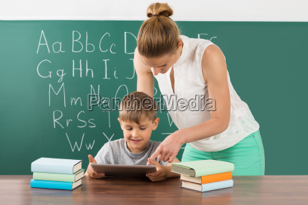 teacher with boy using digital tablet