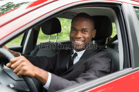 happy businessman driving car