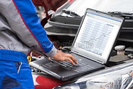 mechaniker mit laptop fuer auto motor