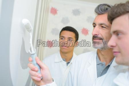 men with roller brush