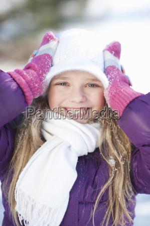 young girl holding onto woolly hat