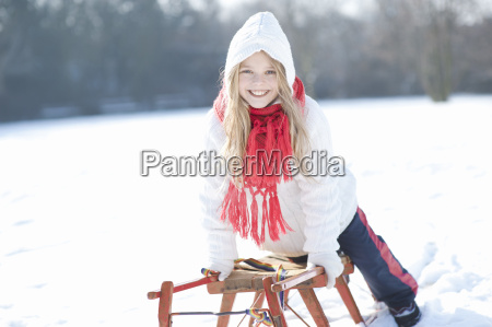 young girl leaning on sledge smiling