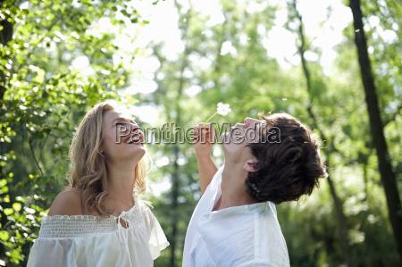 young woman watching man blow dandelion