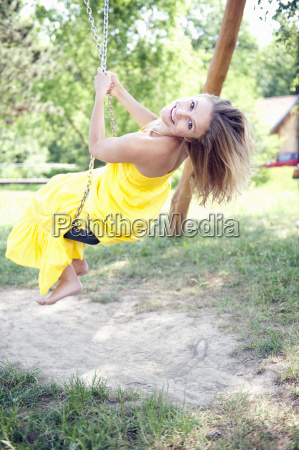 portrait of young woman on swing
