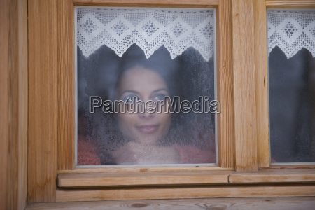 mid adult woman looking though window