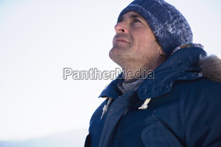mature man in woolly hat looking