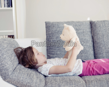 young girl holding teddy bear on