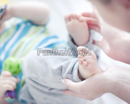 teenage girl touching babys feet