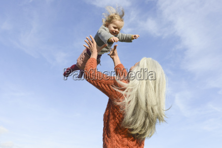 mature woman playing with granddaughter against