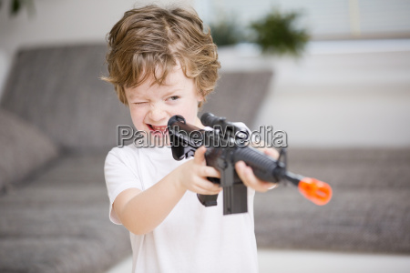 boy aiming with toy gun close